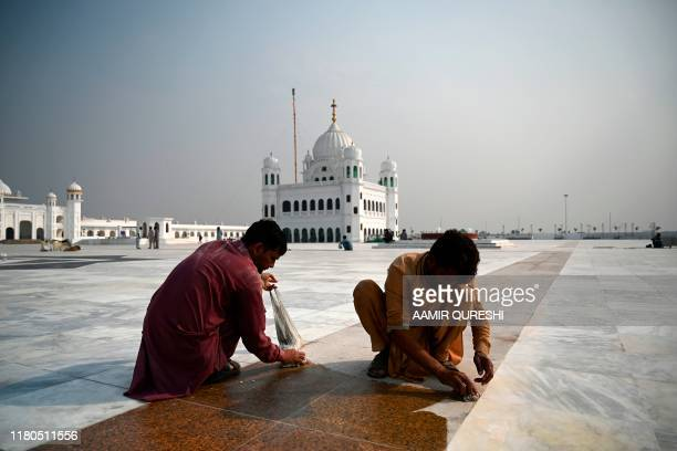 In this picture taken on November 6 2019 workers shine a floor at the Shrine of Baba Guru Nanak Dev at the Gurdwara Darbar Sahib ahead of its opening...