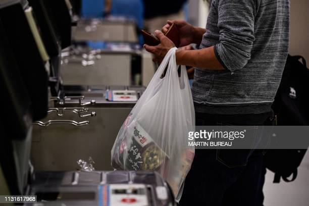 In this picture taken on November 7 a man carries a plastic bag while shopping in a supermarket in Chiba From bento boxes to individually wrapped...