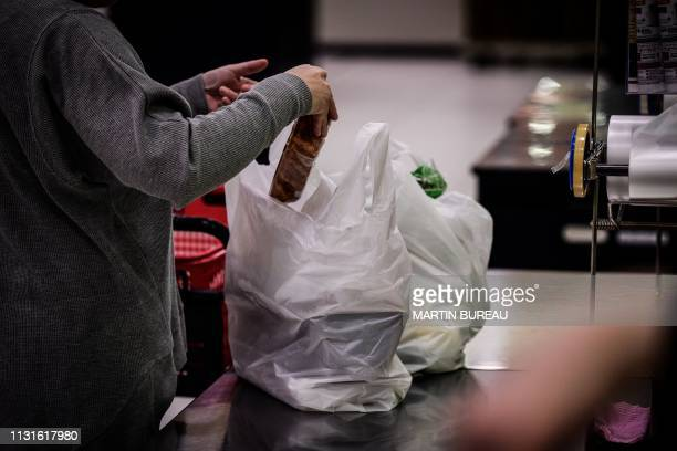 In this picture taken on November 7 a woman packs her shopping into a plastic bag in a supermarket in Chiba. - From bento boxes to individually...