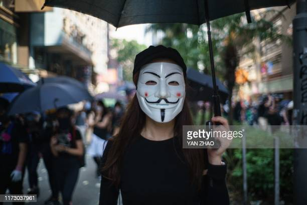 In this picture taken on October 1 a protester wears a Guy Fawkes mask to cover her face, popularised by the V For Vendetta comic book film, in Hong...