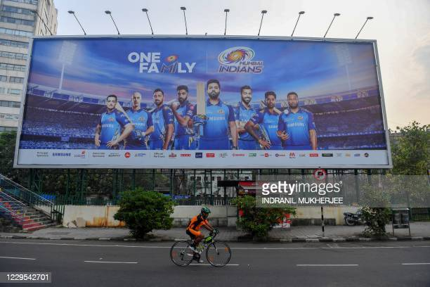 In this picture taken on October 10 a cyclist rides past a hoarding of Mumbai Indians cricketers of the Indian Premier League cricket tournament in...