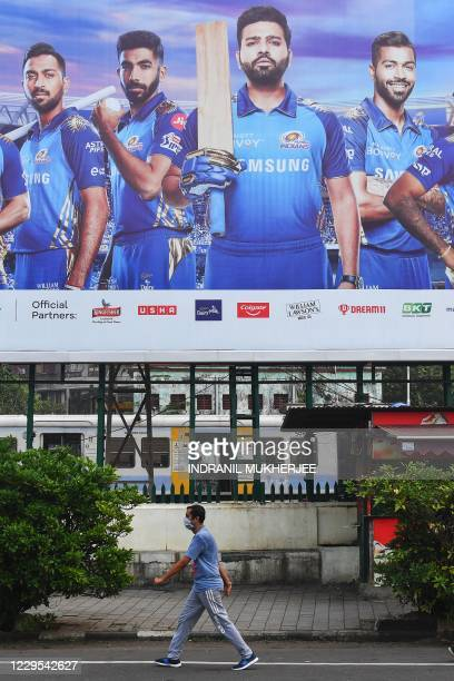 In this picture taken on October 10 a fitness enthusiast walks past a hoarding of Mumbai Indians cricketers of the Indian Premier League cricket...