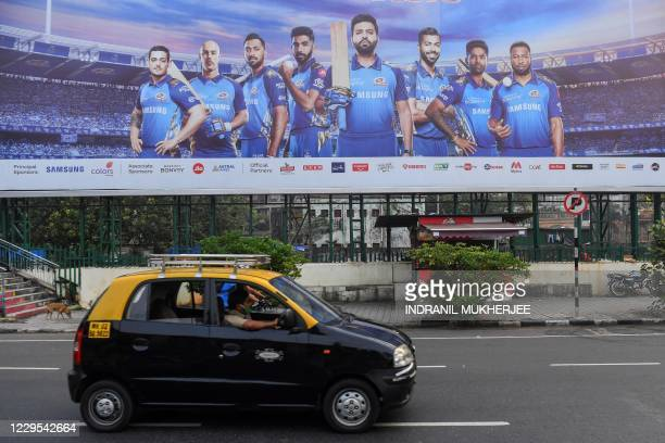 In this picture taken on October 10 a taxi drives past a hoarding of Mumbai Indians cricketers of the Indian Premier League cricket tournament in...