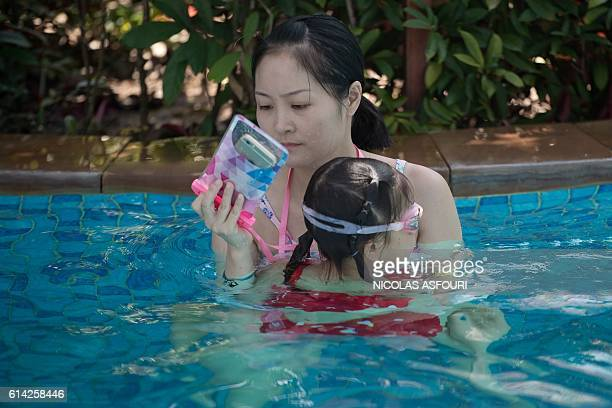 In this picture taken on October 12 2016 a woman looks at her smartphone as she holds a girl in a pool at the Club Med resort in Sanya Almost two...