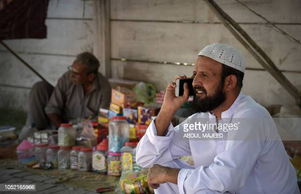 In this picture taken on October 13 2018 a Pakistani resident talks on his smartphone in Peshawar