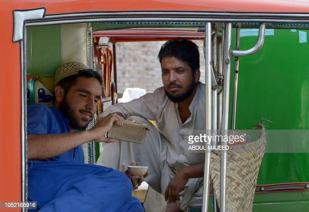 In this picture taken on October 13 2018 Pakistani autorickshaw drivers watch a video on a smartphone in Peshawar