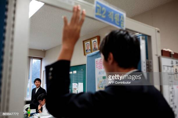 TOPSHOT In this picture taken on October 13 a student raises a hand to enter the class room as portraits of late North Korean leaders Kim Il Sung and...