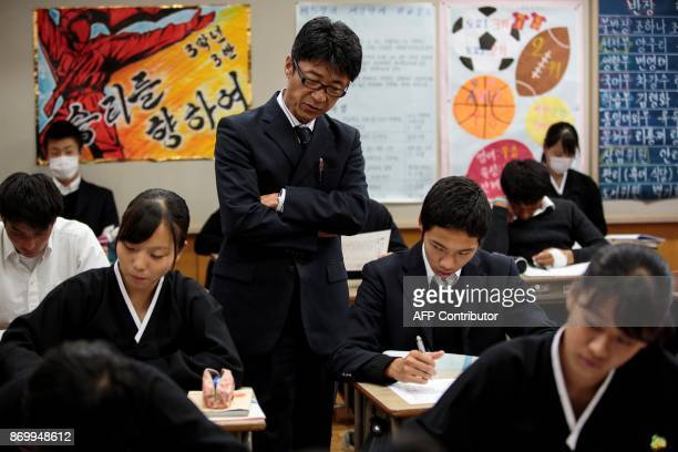 TOPSHOT In this picture taken on October 13 a teacher observes his students as they take an exam at Tokyo Korean high school in Tokyo Portraits of...