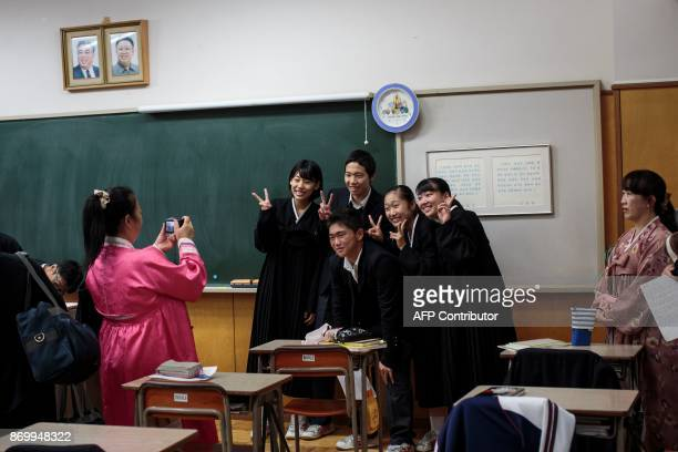 In this picture taken on October 13 Hwang SongWi takes a picture with his classmates under portraits of late North Korean leaders Kim Il Sung and Kim...