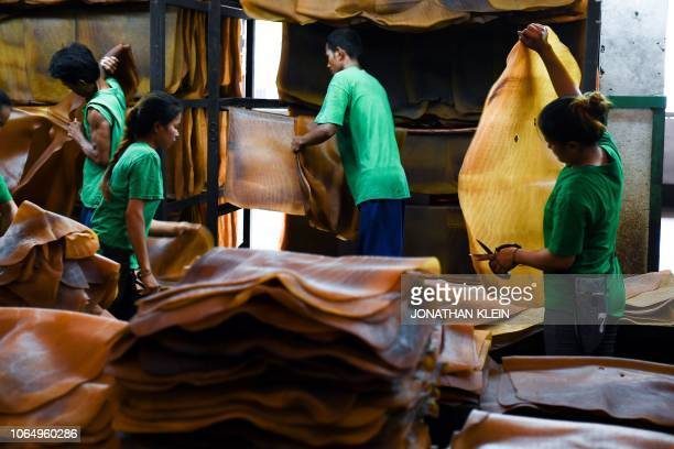 TOPSHOT In this picture taken on October 17 2018 workers sort out raw rubber sheets at a factory in Rayong Province They work in the predawn gloom...
