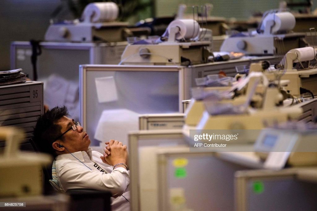 In this picture taken on October 17, 2017, a trader relaxes in his chair on the trading floor at the Hong Kong Stock Exchange. In its heyday in the 1980s, more than a thousand brokers dressed in signature red blazers made deals on the trading floor of the Hong Kong Stock Exchange, in what was a raucous, competitive bear pit. With just a handful of traders remaining, the historic hall will close at the end of the month. / AFP PHOTO / Anthony WALLACE / TO GO WITH Hong Kong-economy-finance-trading-business, FOCUS by Elaine YU
