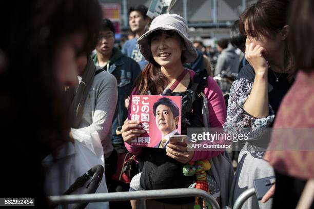 In this picture taken on October 18 a woman holds an electoral leaflet of Japan's Prime Minister and ruling Liberal Democratic Party president Shinzo...