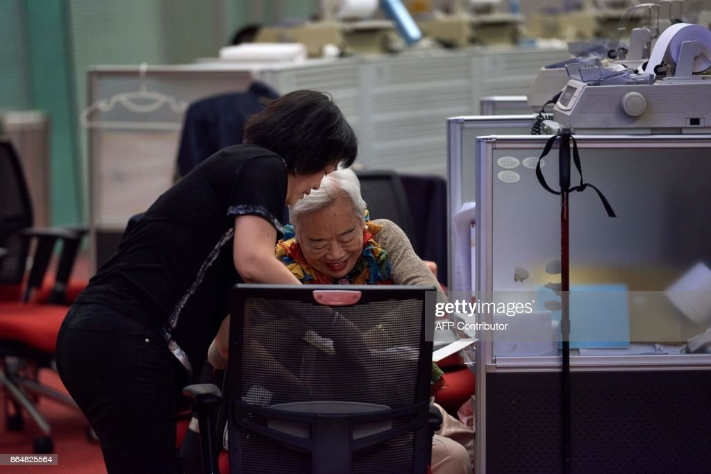 In this picture taken on October 19, 2017, Cheung (L), a trader who worked on the floor since 1994, offers cake to a colleague as she prepares to leave on her last day of work at the Hong Kong Stock Exchange. In its heyday in the 1980s, more than a thousand brokers dressed in signature red blazers made deals on the trading floor of the Hong Kong Stock Exchange, in what was a raucous, competitive bear pit. With just a handful of traders remaining, the historic hall will close at the end of the month. / AFP PHOTO / Anthony WALLACE / TO GO WITH Hong Kong-economy-finance-trading-business, FOCUS by Elaine YU / The erroneous mention[s] appearing in the metadata of this photo by Anthony WALLACE has been modified in AFP systems in the following manner: [Cheung] instead of [Cheng]. Please immediately remove the erroneous mention[s] from all your online services and delete it (them) from your servers. If you have been authorized by AFP to distribute it (them) to third parties, please ensure that the same actions are carried out by them. Failure to promptly comply with these instructions will entail liability on your part for any continued or post notification usage. Therefore we thank you very much for all your attention and prompt action. We are sorry for the inconvenience this notification may cause and remain at your disposal for any further information you may require.