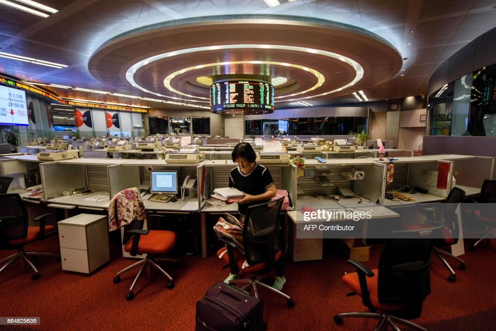 In this picture taken on October 19, 2017, Cheung, a trader who worked on the floor since 1994, packs her belongings as she prepares to leave after her last day of work at the Hong Kong Stock Exchange. In its heyday in the 1980s, more than a thousand brokers dressed in signature red blazers made deals on the trading floor of the Hong Kong Stock Exchange, in what was a raucous, competitive bear pit. With just a handful of traders remaining, the historic hall will close at the end of the month. / AFP PHOTO / Anthony WALLACE / TO GO WITH Hong Kong-economy-finance-trading-business, FOCUS by Elaine YU / The erroneous mention[s] appearing in the metadata of this photo by Anthony WALLACE has been modified in AFP systems in the following manner: [Cheung] instead of [Cheng]. Please immediately remove the erroneous mention[s] from all your online services and delete it (them) from your servers. If you have been authorized by AFP to distribute it (them) to third parties, please ensure that the same actions are carried out by them. Failure to promptly comply with these instructions will entail liability on your part for any continued or post notification usage. Therefore we thank you very much for all your attention and prompt action. We are sorry for the inconvenience this notification may cause and remain at your disposal for any further information you may require.