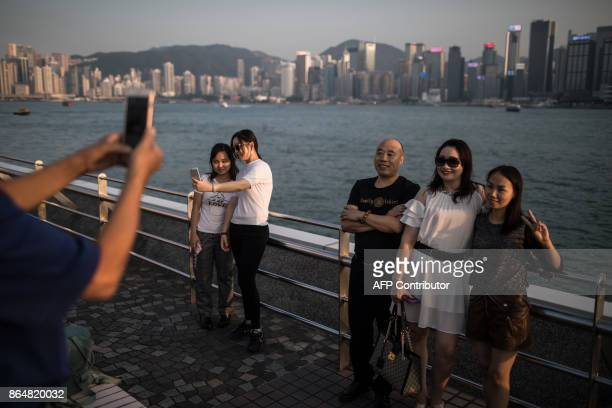 In this picture taken on October 21 tourists pose for photographs on a promenade in front of the city skyline in Hong Kong / AFP PHOTO / DALE DE LA...