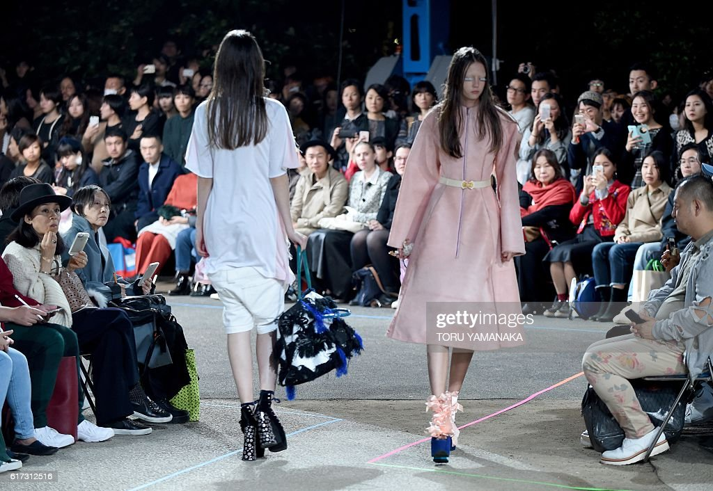 In this picture taken on October 22, 2016, models present creations of MIKIO SAKABE designed by Mikio Sakabe and Shueh Jen-Fang during the 2017 Spring/Summer Collection show at Tokyo Fashion Week. The Marc Jacobs of Japan, singing cats and models cloaked into armour: J-pop and science fiction transformed Tokyo Fashion Week spring/summer 2017 into a style fest unlike any other. / AFP / TORU
