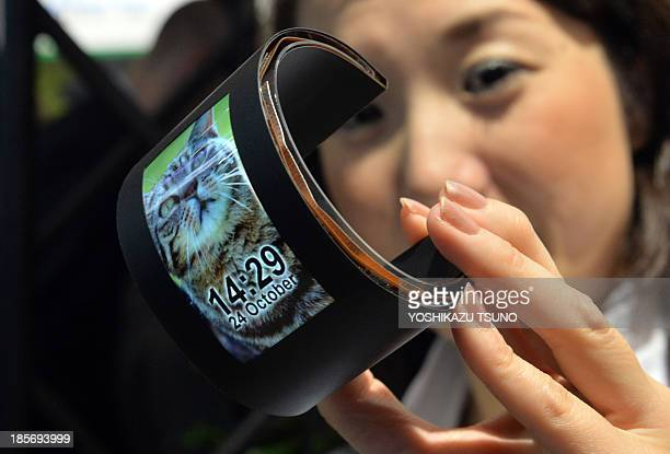 In this picture taken on October 23 Japan's hightech venture Semiconductor Energy Laboratory employee displays a 34inch sized flexible organic light...