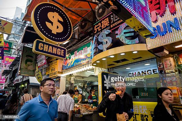 In this picture taken on October 25 2013 pedestrians walk past a money exchange booth in Hong Kong The US Treasury said on October 30 2013 that the...