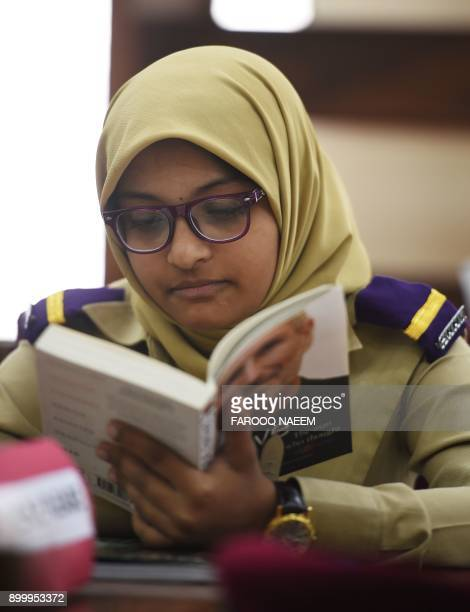 In this picture taken on October 25 Affifa Alam a Pakistani cadet reads a book in a library at the Pakistan Army's first Girls' Cadet College in...