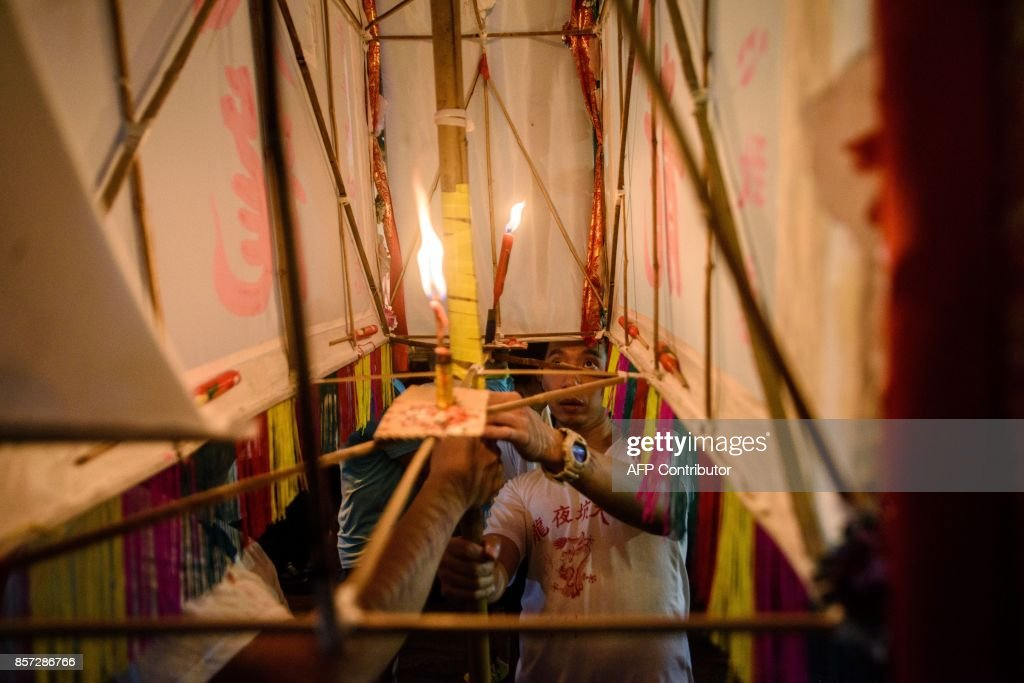In this picture taken on October 3, 2017, a participant looks into a large paper lantern after lighting a candle before the annual Tai Hang 'fire dragon' event, one of the highlights of the city's mid-autumn festival, in Hong Kong. Throngs of festival-goers packed a historic neighbourhood of Hong Kong this week to watch a 'fire dragon' lit with incense sticks dance through the streets in a century-old ritual. / AFP PHOTO / Anthony WALLACE