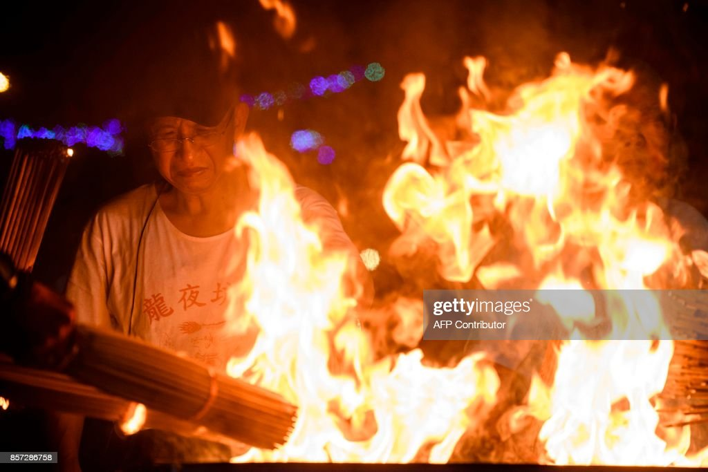 In this picture taken on October 3, 2017, participants light incense sticks in a large fire as they prepare for the annual Tai Hang 'fire dragon' event, one of the highlights of the city's mid-autumn festival, in Hong Kong. Throngs of festival-goers packed a historic neighbourhood of Hong Kong this week to watch a 'fire dragon' lit with incense sticks dance through the streets in a century-old ritual. / AFP PHOTO / Anthony WALLACE