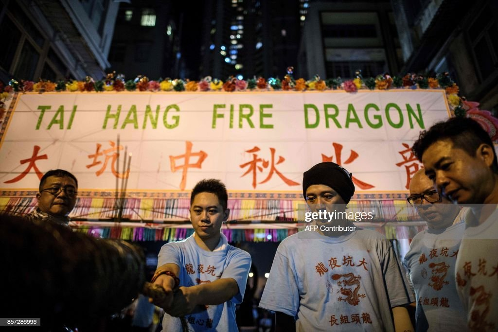 In this picture taken on October 3, 2017, participants prepare for the annual Tai Hang 'fire dragon' event, one of the highlights of the city's mid-autumn festival, in Hong Kong. Throngs of festival-goers packed a historic neighbourhood of Hong Kong this week to watch a 'fire dragon' lit with incense sticks dance through the streets in a century-old ritual. / AFP PHOTO / Anthony WALLACE