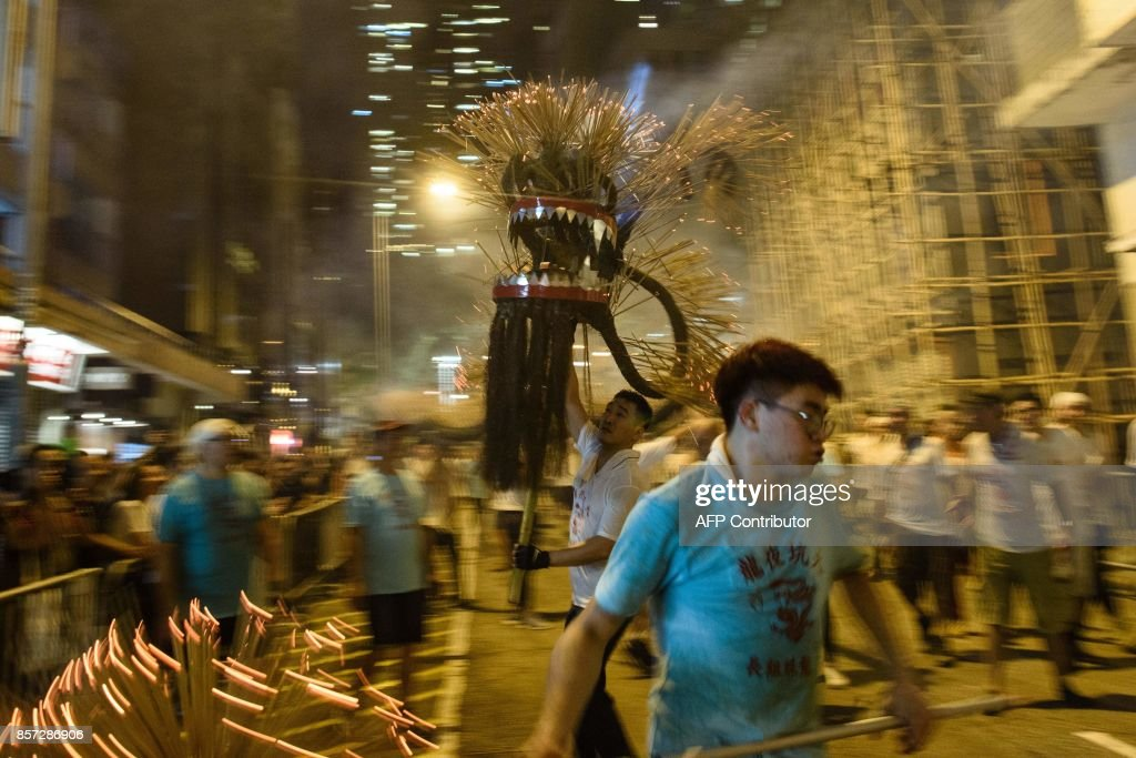In this picture taken on October 3, 2017, participants take part in the annual Tai Hang 'fire dragon' event, one of the highlights of the city's mid-autumn festival, in Hong Kong. Throngs of festival-goers packed a historic neighbourhood of Hong Kong this week to watch a 'fire dragon' lit with incense sticks dance through the streets in a century-old ritual. / AFP PHOTO / Anthony WALLACE
