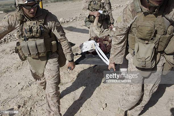 In this picture taken on October 31 2011 and cleared on December 202011 by the US Army shows US Marines carrying a severely wounded Marine who was...