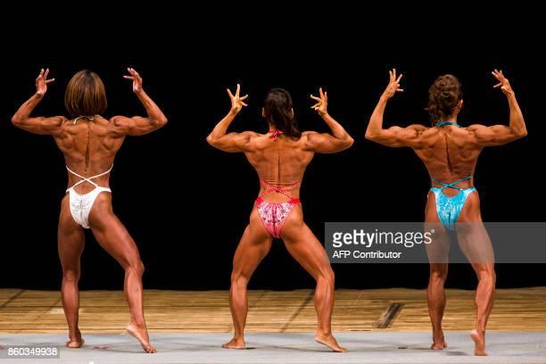 In this picture taken on October 9 Japanese bodybuilders Megumi Sawada Naoko Osawa and Eriko Shimizu pose during the Japan bodybuilding championships...