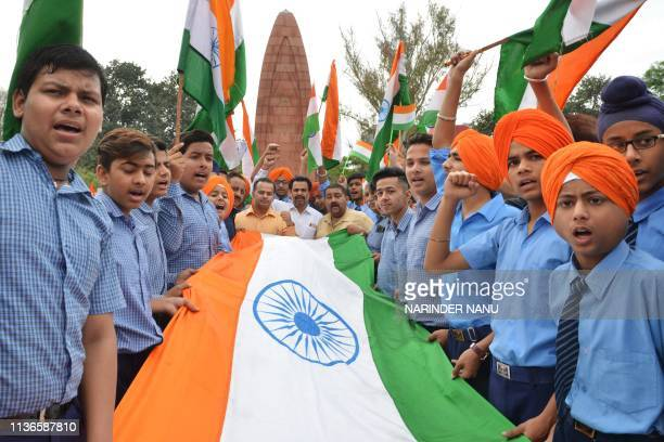 In this picture taken on on April 12 Indian school students hold Indian national flag as they pay tribute to the Jallianwala Bagh massacre martyrs'...