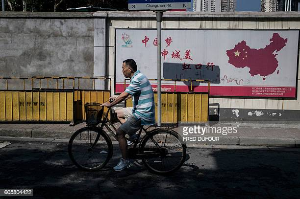 In this picture taken on September 12 a man rides his bicycle in front of a map of China in the North Sichuan Road district in Shanghai / AFP / FRED...