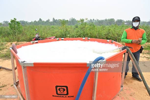 In this picture taken on September 14 2019 a member of the firefighters stands next to a water container in Kampar The number of blazes in...