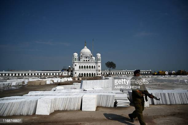 In this picture taken on September 16 2019 a Pakistani policeman walk past stacks of marble on the construction site at the Sikh religious site...
