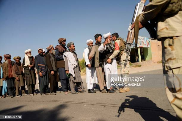 In this picture taken on September 18 2019 an Afghan soldier frisks supporters arriving for a campaign rally of presidential candidate Gulbuddin...