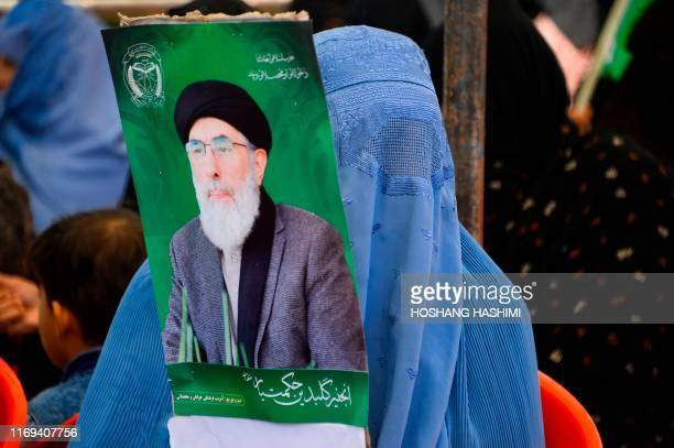 In this picture taken on September 18 2019 An woman holds an electoral poster of presidential candidate Gulbuddin Hekmatyar during a campaign rally...