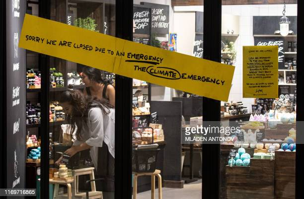 In this picture taken on September 19 employees arrange a display behind a sign warning customers of a climate strike closure of a skin care shop in...