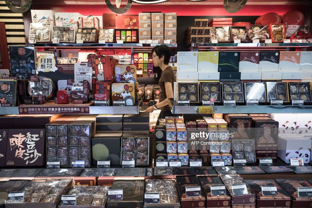 In this picture taken on September 2, 2017, a woman walks past mooncakes (front) for sale at a bakery inside a train station in Hong Kong. It is one of Hong Kong's most treasured food traditions: the buying, giving and eating of 'mooncakes' to mark mid-autumn festival, celebrated in Chinese communities around the world in October. / AFP PHOTO / Dale DE LA REY / TO GO WITH HongKong-lifestyle-culture-food-mooncake by Laura Mannering