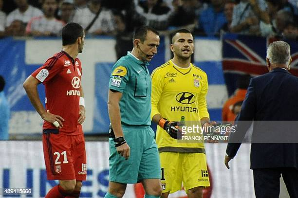 In this picture taken on September 20 2015 Referee Ruddy Buquet calls for a match interruption after crowd trouble during during the French L1...