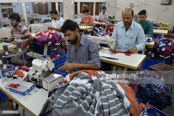 In this picture taken on September 25 Indian men work at a garment factory in Ludhiana Over the last year India's Prime Minister Narendra Modi has...