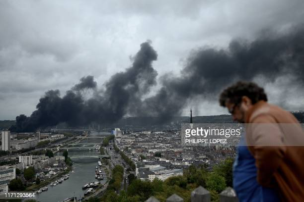 TOPSHOT In this picture taken on September 26 2019 in Bonsecours a man looks at smoke billowing from a Seveso classified Lubrizol factory on fire in...