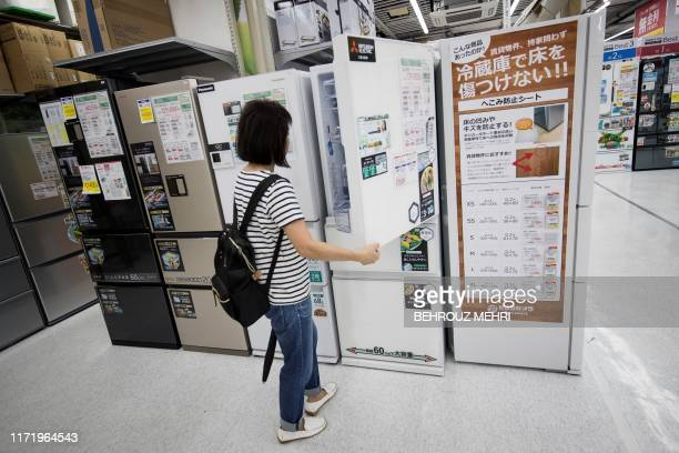 In this picture taken on September 26 a costumer checks a refrigerator displayed at a department store in Tokyo From October 1 Japan finally...