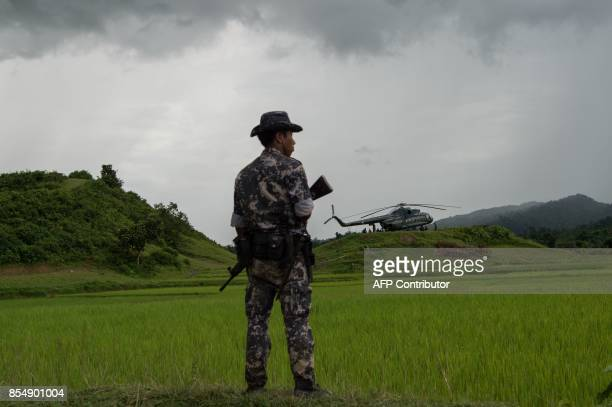 TOPSHOT In this picture taken on September 27 a policeman stands guard near a military transport helicopter at Ye Baw Kyaw village Maungdaw in...