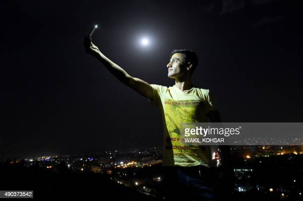 In this picture taken on September 27 an Afghan man is illuminated by the light from his phone while taking a selfie on the top of the Wazir Akbar...