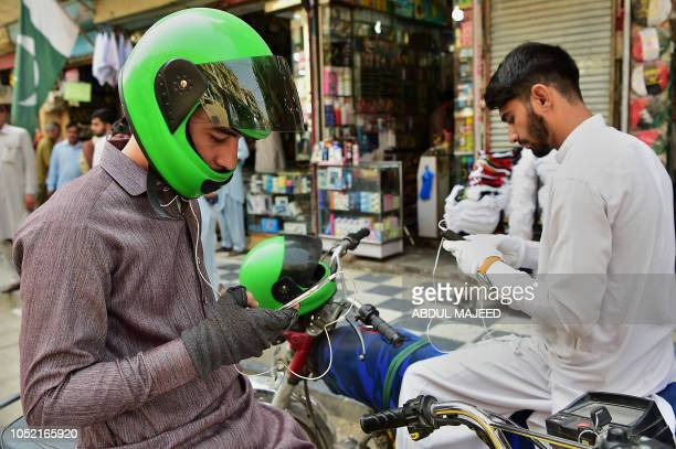 In this picture taken on September 29 2018 Pakistani motorbike taxi riders look at their smartphones alongside a street in Peshawar