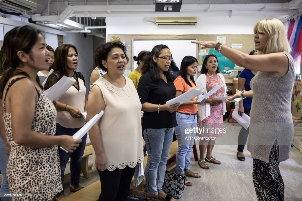 In this picture taken on September 3, 2017, 'Unsung Heroes' choir founder Jane Englemann (R) leads her group of Filipina domestic workers during a practice session inside a kindergarten school's classroom in Hong Kong. Each Sunday, a choir of Filipina domestic workers in Hong Kong gathers to sing songs that remind them of the children they left back home. Known as the 'Unsung Heroes', what began as a group of shy performers now regularly take the stage around Hong Kong and feature in a new documentary about the lives of the city's maids, known locally as 'helpers'. / AFP PHOTO / DALE DE LA REY / To go with AFP story Hong Kong-Philippines-music-social-film-maids , Feature by Laura Mannering