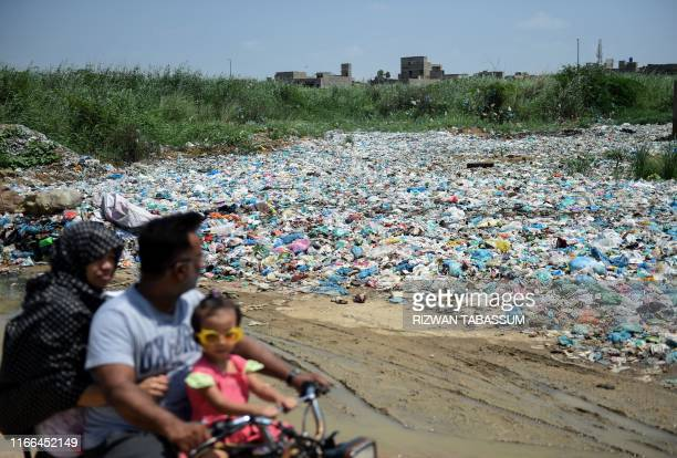 In this picture taken on September 4 2019 a family rides past a garbage dump at a residential area in Pakistan's port city of Karachi Swarms of flies...
