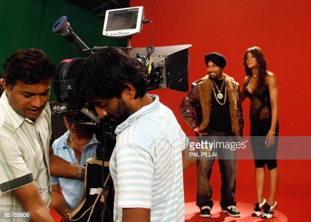 In this picture taken on September 5 Indian camera assistants shift a camera during the filming of a musical number on a set at Kamlistan Studio in...