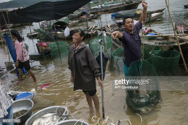 In this picture taken on September 7 a couple from the Tanka community sell fish on the shore in Datang in southern China's Guangdong province Along...