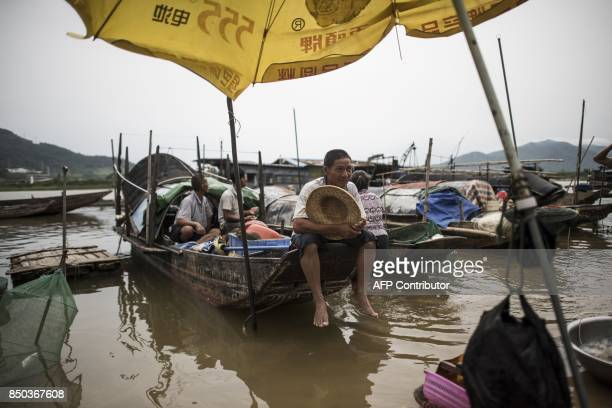 In this picture taken on September 7 a man from the Tanka community sits on a boat as he waits for customers to buy fish in Datang in southern...