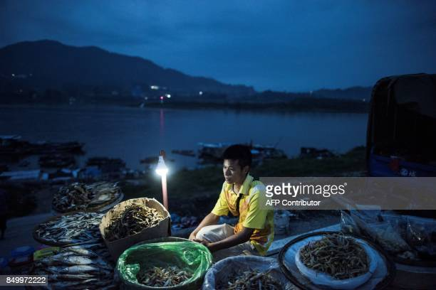 In this picture taken on September 7 a man sells dried fish on the shore next to moored boats from the Tanka community in Datang southern China's...